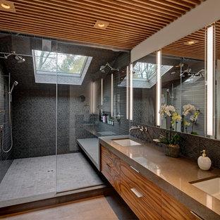 シカゴのコンテンポラリースタイルのおしゃれな浴室 (フラットパネル扉のキャビネット、中間色木目調キャビネット、アルコーブ型シャワー、黒いタイル、白い壁、アンダーカウンター洗面器、グレーの床、開き戸のシャワー、グレーの洗面カウンター、洗面台2つ) の写真