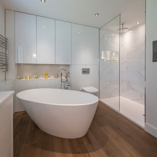 Contemporary ensuite bathroom in Surrey with freestanding cabinets, white cabinets, a freestanding bath, a corner shower, a wall mounted toilet, grey tiles, white tiles, white walls, brown floors and an open shower.