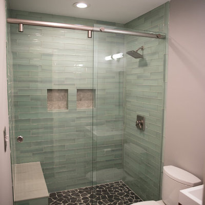 Inspiration for a mid-sized transitional 3/4 green tile and ceramic tile ceramic tile and beige floor bathroom remodel in Indianapolis with dark wood cabinets, a two-piece toilet, gray walls, an integrated sink, flat-panel cabinets and solid surface countertops