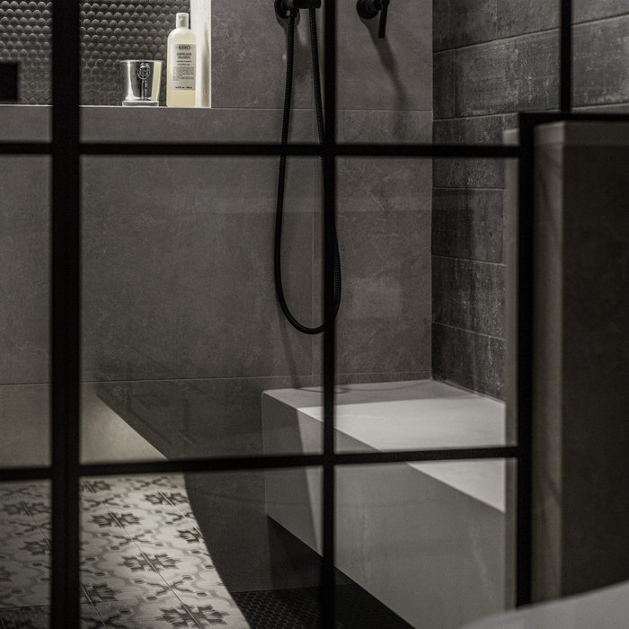Sauna - mid-sized industrial beige tile and porcelain tile porcelain tile and multicolored floor sauna idea in Detroit with shaker cabinets, black cabinets, a one-piece toilet, gray walls, an undermou