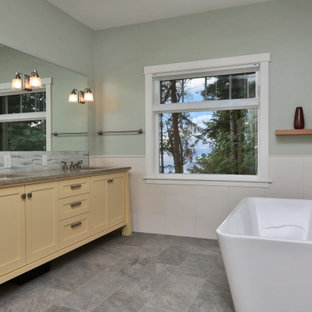 Bathroom - large contemporary master white tile and porcelain tile gray floor bathroom idea in Seattle with shaker cabinets, yellow cabinets, a two-piece toilet, green walls, an undermount sink, concrete countertops and gray countertops