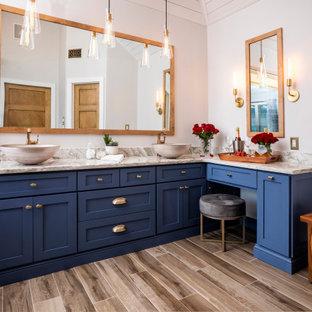 Ispirazione per una stanza da bagno classica con ante in stile shaker, ante blu, vasca freestanding, pareti bianche, pavimento in legno massello medio, lavabo a bacinella, pavimento marrone e top multicolore