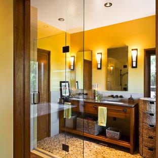 Diseño de cuarto de baño asiático con lavabo bajoencimera, armarios con paneles lisos, puertas de armario de madera en tonos medios, ducha empotrada, baldosas y/o azulejos beige, paredes amarillas, suelo de baldosas tipo guijarro y suelo beige