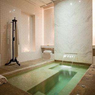 Cette image montre une très grand salle de bain principale design avec un bain bouillonnant, un carrelage blanc, un carrelage métro, un mur blanc et un sol marron.