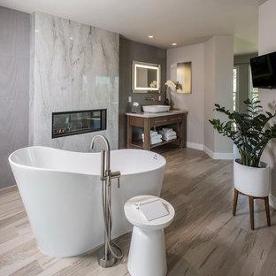 Imagen de cuarto de baño principal, actual, grande, con armarios abiertos, puertas de armario de madera en tonos medios, bañera exenta, baldosas y/o azulejos blancos, baldosas y/o azulejos de mármol, paredes grises, suelo vinílico, lavabo sobreencimera, suelo gris y encimeras blancas