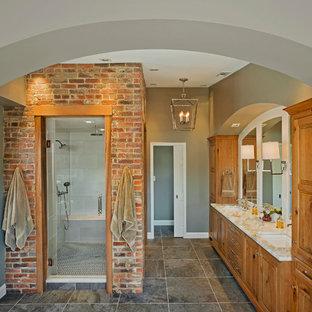 Imagen de cuarto de baño principal, clásico renovado, grande, con lavabo bajoencimera, armarios con paneles con relieve, puertas de armario de madera oscura, encimera de mármol, baldosas y/o azulejos grises y baldosas y/o azulejos de porcelana
