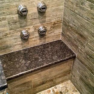Foto di una stanza da bagno padronale tropicale di medie dimensioni con ante con riquadro incassato, ante grigie, doccia alcova, WC monopezzo, piastrelle grigie, piastrelle in gres porcellanato, pavimento in gres porcellanato, lavabo a bacinella e top in granito