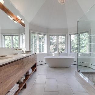 フィラデルフィアの大きいコンテンポラリースタイルのおしゃれなマスターバスルーム (アンダーカウンター洗面器、フラットパネル扉のキャビネット、淡色木目調キャビネット、置き型浴槽、アルコーブ型シャワー、白い壁、分離型トイレ、白いタイル、石スラブタイル、スレートの床、珪岩の洗面台、グレーの床、開き戸のシャワー) の写真