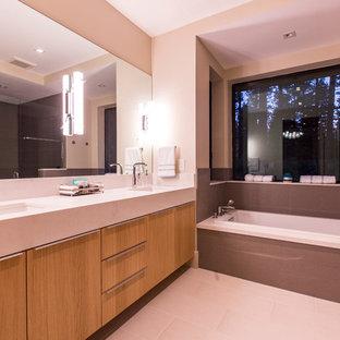 Immagine di una stanza da bagno contemporanea con ante lisce, ante in legno chiaro, WC monopezzo, pavimento in legno massello medio, top in quarzo composito, vasca da incasso, piastrelle in gres porcellanato, lavabo sottopiano e porta doccia a battente