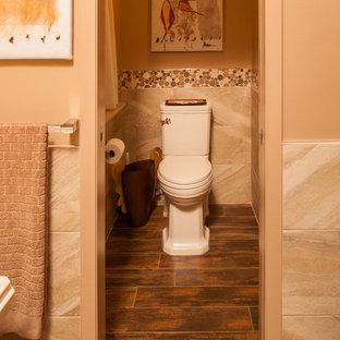 Foto de cuarto de baño principal, asiático, grande, con armarios con paneles lisos, puertas de armario de madera oscura, encimera de cuarzo compacto, bañera exenta, ducha empotrada, baldosas y/o azulejos de porcelana, suelo de baldosas de porcelana, baldosas y/o azulejos beige, sanitario de dos piezas, paredes marrones, lavabo sobreencimera, suelo marrón y ducha con puerta con bisagras