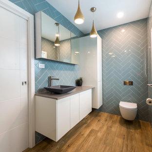Foto di una piccola stanza da bagno con doccia moderna con ante gialle, WC sospeso, piastrelle blu, piastrelle in ceramica, pareti blu, pavimento in vinile, lavabo a bacinella, top in granito, pavimento multicolore, top grigio, un lavabo, mobile bagno sospeso e boiserie