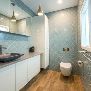 他の地域の小さいモダンスタイルのおしゃれなバスルーム (浴槽なし) (壁掛け式トイレ、青いタイル、セラミックタイル、青い壁、クッションフロア、ベッセル式洗面器、御影石の洗面台、マルチカラーの床、グレーの洗面カウンター、洗面台1つ、フローティング洗面台、羽目板の壁、落し込みパネル扉のキャビネット、白いキャビネット) の写真
