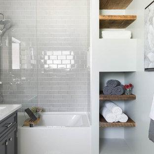 シカゴの中くらいの北欧スタイルのおしゃれなバスルーム (浴槽なし) (レイズドパネル扉のキャビネット、ドロップイン型浴槽、シャワー付き浴槽、分離型トイレ、白いタイル、セラミックタイル、白い壁、モザイクタイル、オーバーカウンターシンク、ソープストーンの洗面台、マルチカラーの床、引戸のシャワー、グレーのキャビネット) の写真