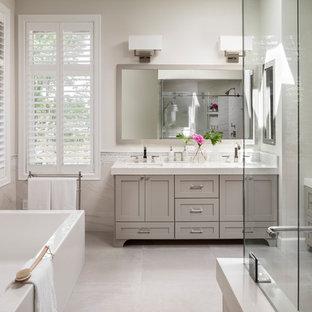 シアトルの巨大なトランジショナルスタイルのおしゃれなマスターバスルーム (シェーカースタイル扉のキャビネット、グレーのキャビネット、置き型浴槽、段差なし、ビデ、磁器タイルの床、アンダーカウンター洗面器、クオーツストーンの洗面台、グレーの床、引戸のシャワー、白い洗面カウンター) の写真