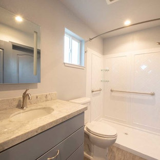 Inspiration for a small arts and crafts bathroom in San Francisco with flat-panel cabinets, grey cabinets, a one-piece toilet, white walls, laminate floors, an undermount sink, engineered quartz benchtops, grey floor, a shower curtain and grey benchtops.