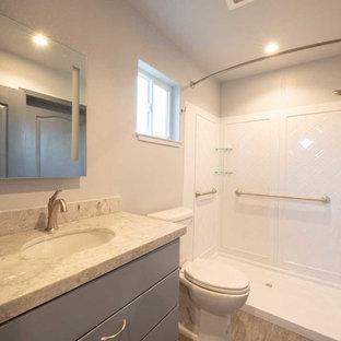 Ejemplo de cuarto de baño de estilo americano, pequeño, con armarios con paneles lisos, puertas de armario grises, sanitario de una pieza, paredes blancas, suelo laminado, lavabo bajoencimera, encimera de cuarzo compacto, suelo gris, ducha con cortina y encimeras grises