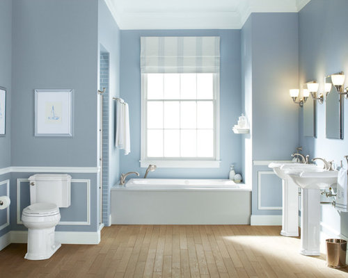 midsized elegant master light wood floor alcove bathtub photo in milwaukee with a pedestal