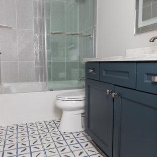 Diseño de cuarto de baño principal, actual, de tamaño medio, con armarios estilo shaker, puertas de armario azules, bañera esquinera, combinación de ducha y bañera, sanitario de una pieza, baldosas y/o azulejos grises, baldosas y/o azulejos de mármol, paredes blancas, suelo con mosaicos de baldosas, lavabo bajoencimera y ducha con puerta con bisagras