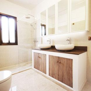 Immagine di una stanza da bagno con doccia contemporanea di medie dimensioni con lavabo a bacinella, ante in legno scuro, doccia a filo pavimento, WC monopezzo, consolle stile comò, piastrelle in ceramica, pareti beige, pavimento in travertino, top in superficie solida e top marrone