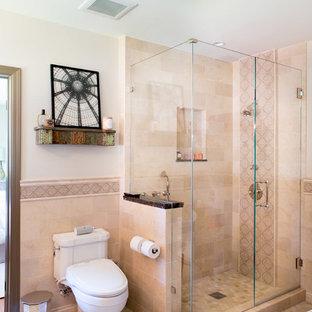 На фото: главная ванная комната в средиземноморском стиле с угловым душем, раздельным унитазом, бежевой плиткой и бежевыми стенами с
