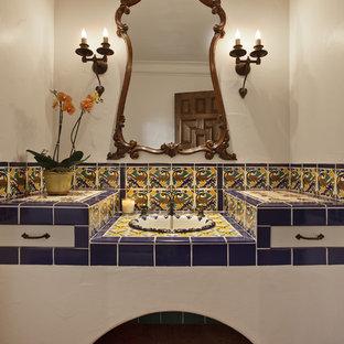 На фото: ванная комната в средиземноморском стиле с накладной раковиной, разноцветной плиткой, керамической плиткой, столешницей из плитки, белыми стенами и полом из терракотовой плитки с