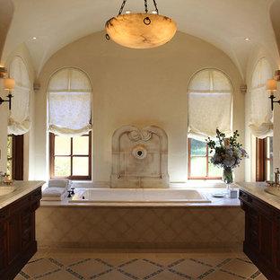 Ejemplo de cuarto de baño principal, mediterráneo, grande, con armarios con paneles empotrados, puertas de armario de madera en tonos medios, bañera encastrada, baldosas y/o azulejos marrones, baldosas y/o azulejos de cerámica, paredes marrones, lavabo bajoencimera, encimera de mármol y encimeras grises