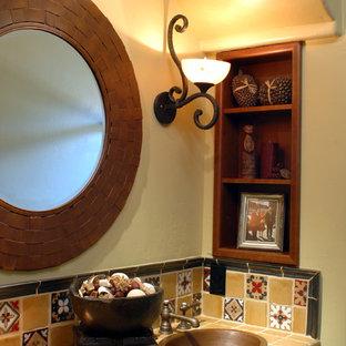 Klassisk inredning av ett mellanstort badrum med dusch, med ett nedsänkt handfat, luckor med upphöjd panel, skåp i mellenmörkt trä, kaklad bänkskiva, gul kakel, keramikplattor, gula väggar och travertin golv