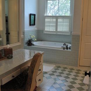 オースティンの広いサンタフェスタイルのおしゃれなマスターバスルーム (白いキャビネット、アルコーブ型浴槽、アルコーブ型シャワー、セラミックタイル、オーバーカウンターシンク、タイルの洗面台、フラットパネル扉のキャビネット、青いタイル、緑のタイル、白いタイル、ベージュの壁、セラミックタイルの床) の写真