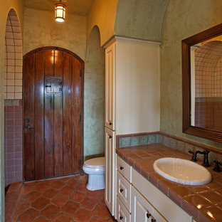 Example of a tuscan terra-cotta floor bathroom design in Austin with a drop-in sink