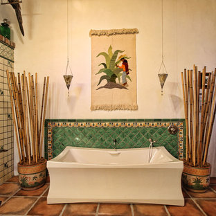 Photo of a bathroom in Los Angeles with a freestanding tub, green tile, beige walls and terra-cotta floors.