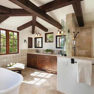 Inspiration for a large mediterranean ensuite bathroom in Santa Barbara with a submerged sink, recessed-panel cabinets, medium wood cabinets, a freestanding bath, a walk-in shower, beige tiles, ceramic tiles and beige walls.