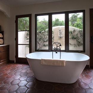 Modelo de cuarto de baño principal, mediterráneo, de tamaño medio, con armarios con paneles empotrados, puertas de armario de madera en tonos medios, encimera de piedra caliza y baldosas y/o azulejos beige
