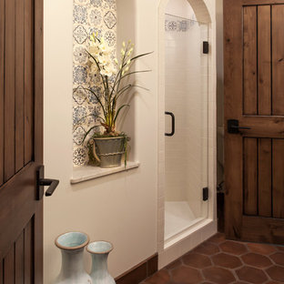 Photo of a large mediterranean 3/4 bathroom in Santa Barbara with an undermount sink, recessed-panel cabinets, dark wood cabinets, an alcove shower, a two-piece toilet, beige tile, terra-cotta tile, white walls and terra-cotta floors.