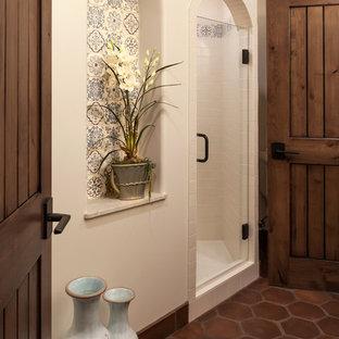 Пример оригинального дизайна: большая ванная комната в средиземноморском стиле с врезной раковиной, фасадами с утопленной филенкой, темными деревянными фасадами, душем в нише, раздельным унитазом, бежевой плиткой, терракотовой плиткой, белыми стенами, полом из терракотовой плитки и душевой кабиной