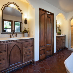 Design ideas for a large mediterranean ensuite bathroom with a submerged sink, recessed-panel cabinets, dark wood cabinets, limestone worktops, a freestanding bath, an alcove shower, a two-piece toilet, beige tiles, terracotta tiles, white walls and terracotta flooring.