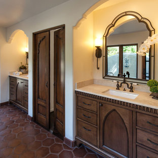 Large tuscan master beige tile and terra-cotta tile terra-cotta floor bathroom photo in Santa Barbara with an undermount sink, recessed-panel cabinets, dark wood cabinets, limestone countertops, a two-piece toilet and white walls