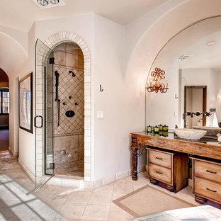 Ejemplo de cuarto de baño principal, mediterráneo, de tamaño medio, con puertas de armario con efecto envejecido, ducha esquinera, baldosas y/o azulejos beige, baldosas y/o azulejos de piedra, paredes beige, suelo de travertino, lavabo sobreencimera y encimera de vidrio
