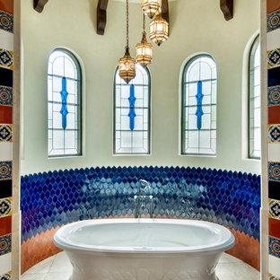ヒューストンの地中海スタイルのおしゃれなマスターバスルーム (置き型浴槽、青いタイル、マルチカラーのタイル、オレンジのタイル、ベージュの床) の写真