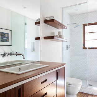 Design ideas for a mediterranean bathroom in Sacramento with beaded cabinets, medium wood cabinets, an alcove shower, a one-piece toilet, white tiles, white walls, medium hardwood flooring, a built-in sink, wooden worktops, brown floors, a hinged door and brown worktops.