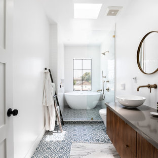 Inspiration for a medium sized mediterranean ensuite bathroom in Los Angeles with flat-panel cabinets, brown cabinets, a freestanding bath, a shower/bath combination, a wall mounted toilet, white tiles, ceramic tiles, white walls, ceramic flooring, a vessel sink, engineered stone worktops, blue floors, a hinged door, grey worktops, double sinks and a floating vanity unit.