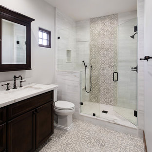 Mediterranes Duschbad mit verzierten Schränken, dunklen Holzschränken, Duschnische, Wandtoilette mit Spülkasten, beigefarbenen Fliesen, grauen Fliesen, weißen Fliesen, grauer Wandfarbe, Unterbauwaschbecken, buntem Boden, Falttür-Duschabtrennung und weißer Waschtischplatte in San Diego