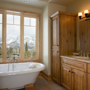 Large mountain style light wood floor and brown floor freestanding bathtub photo in Other with brown cabinets, beige walls and granite countertops