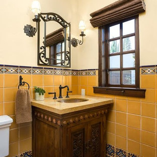 Small tuscan 3/4 multicolored tile and porcelain tile terra-cotta floor bathroom photo in Los Angeles with recessed-panel cabinets, dark wood cabinets, a one-piece toilet, an undermount sink and limestone countertops