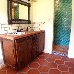 Aménagement d'une salle de bain principale classique avec un lavabo posé, un placard avec porte à panneau surélevé, des portes de placard en bois brun, un plan de toilette en carrelage, une baignoire sur pieds, une douche ouverte, un WC séparé, des carreaux en terre cuite, un mur blanc et un sol en carreau de terre cuite.