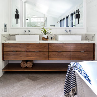 Freestanding bathtub - mediterranean master gray floor freestanding bathtub idea in Sacramento with medium tone wood cabinets, white walls, marble countertops, flat-panel cabinets, a vessel sink and beige countertops
