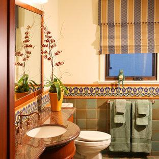 Inredning av ett medelhavsstil badrum, med ett undermonterad handfat, skåp i shakerstil, skåp i mellenmörkt trä, flerfärgad kakel och klinkergolv i terrakotta