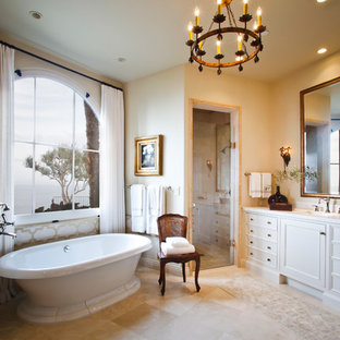 Large tuscan master blue tile and limestone tile limestone floor and beige floor bathroom photo in Los Angeles with recessed-panel cabinets, white cabinets, white walls, an undermount sink, marble countertops, a hinged shower door and white countertops
