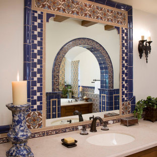 Expansive mediterranean ensuite bathroom in Santa Barbara with a submerged sink, recessed-panel cabinets, dark wood cabinets, a built-in bath, an alcove shower, a two-piece toilet, blue tiles, white walls and limestone flooring.