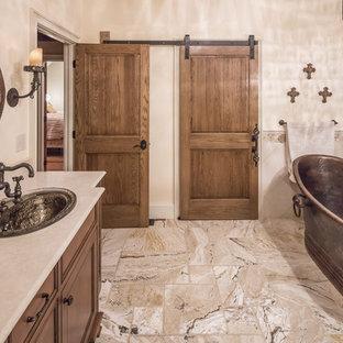 Großes Rustikales Badezimmer En Suite mit Schrankfronten mit vertiefter Füllung, hellbraunen Holzschränken, freistehender Badewanne, Eckdusche, Wandtoilette mit Spülkasten, beigefarbenen Fliesen, Marmorfliesen, schwarzer Wandfarbe, Marmorboden, Einbauwaschbecken, Granit-Waschbecken/Waschtisch, beigem Boden und Falttür-Duschabtrennung in Boston