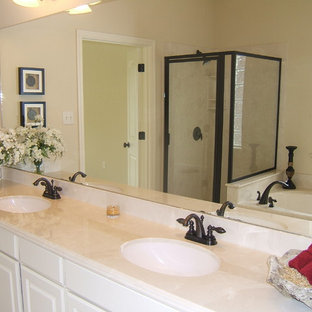 Inspiration for a mid-sized timeless master bathroom remodel in Austin with raised-panel cabinets, white cabinets, beige walls, an undermount sink and a hinged shower door